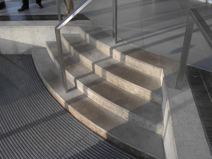 Ortbetontreppe im Foyer, rechts barrierefreie Ebene, links gebogene Sauberlaufzone
